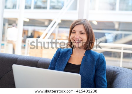 Smiling businesswoman on a couch in office with laptop - stock photo