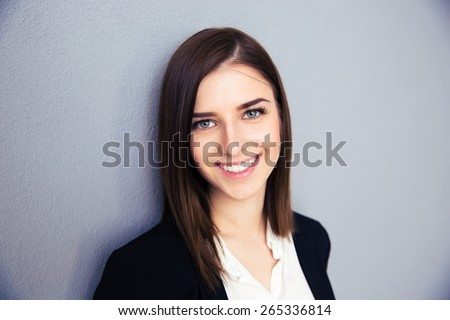 Smiling businesswoman over gray background. Wearing in suit. Looking at camera - stock photo