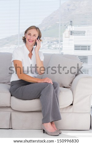 Smiling businesswoman phoning and sitting on sofa