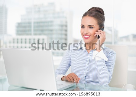 Smiling businesswoman phoning in bright office