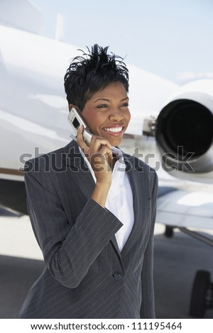 Smiling businesswoman phoning with airplane in background - stock photo