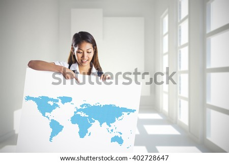Smiling businesswoman pointing a white poster against white room with squares at wall