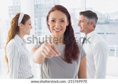 Smiling businesswoman pointing at camera in the office - stock photo
