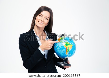 Smiling businesswoman pointing finger on globe isolated on a white background. Looking at camera