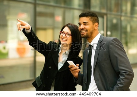 Smiling businesswoman pointing the way to her colleague  - stock photo