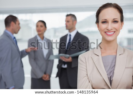 Smiling businesswoman posing while colleagues talking together in bright office