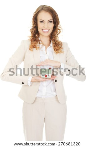 Smiling businesswoman presenting a model house. - stock photo