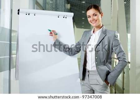 Smiling businesswoman presenting new project on a whiteboard - stock photo