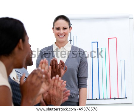 Smiling businesswoman presenting statistics in a company against a white background