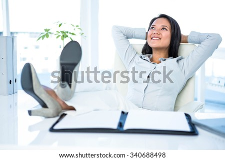 Smiling businesswoman relaxing herself at the desk in work