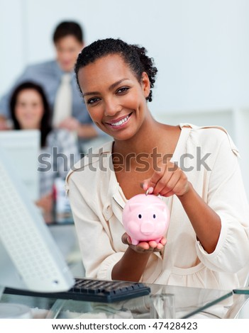 Smiling businesswoman saving money in a piggy-bank at her desk - stock photo