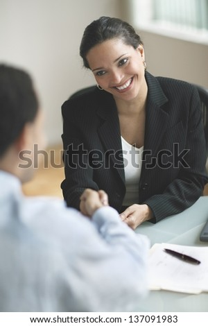Smiling businesswoman shaking hands (soft focus)