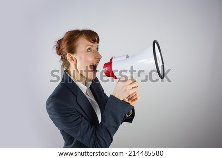 Smiling businesswoman shouting through megaphone on grey background