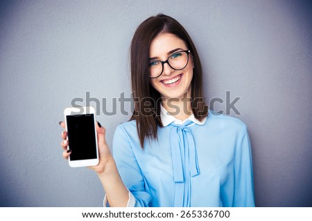 Smiling businesswoman showing blank smartphone screen over gray background. Wearing in blue shirt and glasses. Looking at camera. - stock photo