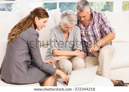 Smiling businesswoman showing laptop monitor to senior couple at home - stock photo