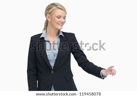 Smiling businesswoman showing something with her finger while looking down