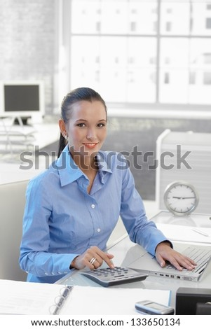 Smiling businesswoman sitting at work, using laptop computer and calculator. - stock photo