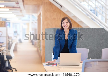 Smiling businesswoman standing at her desk in bright modern offi - stock photo