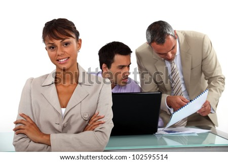 Smiling businesswoman standing in front of male colleagues - stock photo