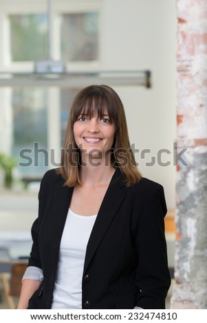 Smiling businesswoman standing indoors in a bright airy office looking at the camera - stock photo