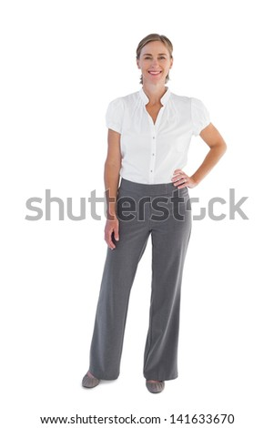 Smiling businesswoman standing with her hand on her hip on white background - stock photo