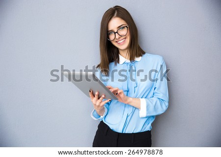 Smiling businesswoman standing with tablet computer over gray background. Wearing in blue shirt and glasses. Looking at camera - stock photo