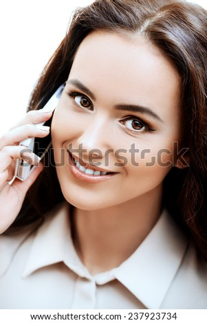 Smiling businesswoman talking on her cellphone in the office. - stock photo