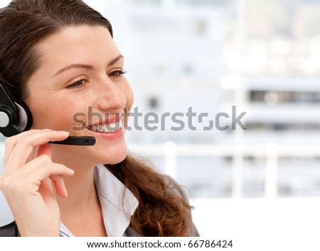 Smiling businesswoman talking on the phone with headphones on in an office