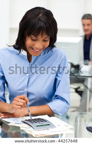 Smiling businesswoman using a calculator in the office - stock photo
