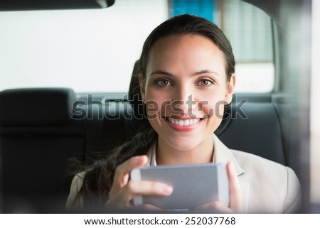 Smiling businesswoman using her phone in her car - stock photo