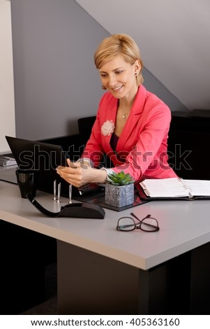 Smiling businesswoman using laptop computer in office, sitting at desk. - stock photo