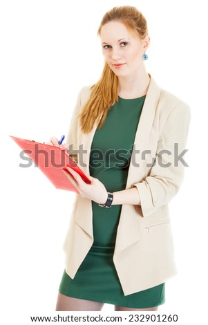 smiling businesswoman wearing a green dress and jacket stands with corrects document - stock photo