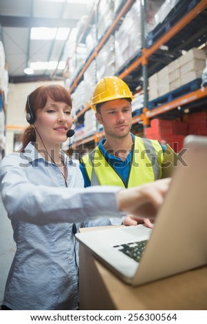 Smiling businesswoman wearing headset using laptop in warehouse - stock photo
