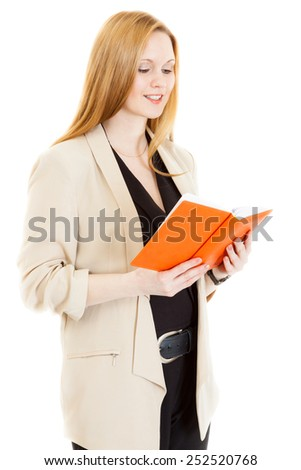 smiling businesswoman wearing jacket reads diary - stock photo