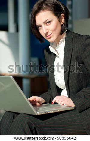 Smiling businesswoman with a laptop - stock photo