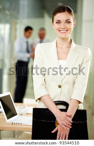 Smiling businesswoman with briefcase looking at camera in working environment