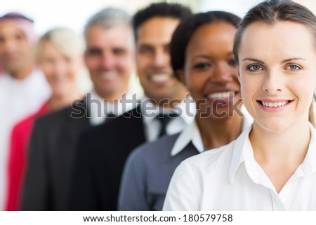 smiling businesswoman with colleagues standing in a row - stock photo