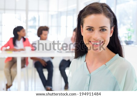 Smiling businesswoman with coworkers in background in the office