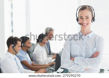 Smiling businesswoman with executives using computers in office - stock photo