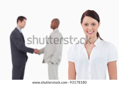 Smiling businesswoman with hand shaking trading partners behind her against a white background