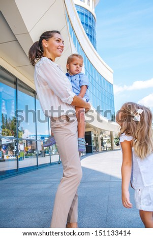 Smiling businesswoman with her two kids near office building - stock photo