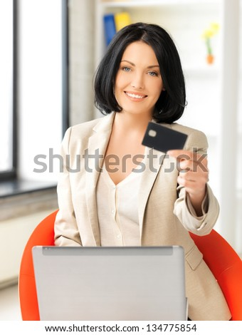 smiling businesswoman with laptop showing credit card - stock photo