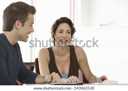 Smiling businesswoman with male colleague in meeting room - stock photo