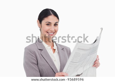 Smiling businesswoman with news paper against a white background - stock photo