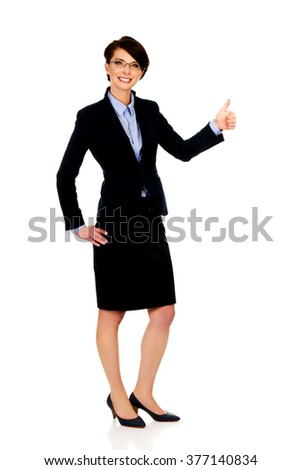 Smiling businesswoman with thumbs up. - stock photo