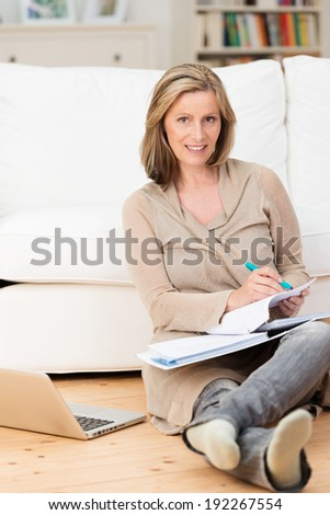 Smiling businesswoman working from home sitting comfortably on the floor of her living room with paperwork on her lap and her laptop computer on the floor alongside her - stock photo