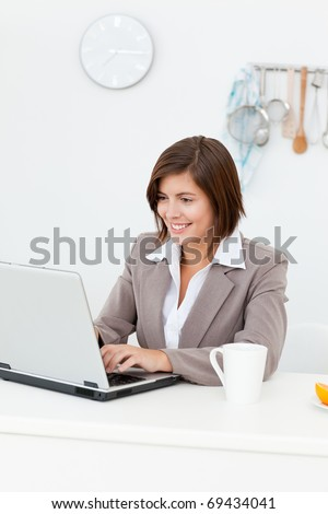 Smiling businesswoman working on her laptop at home - stock photo