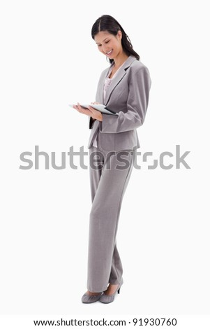 Smiling businesswoman working on tablet against a white background