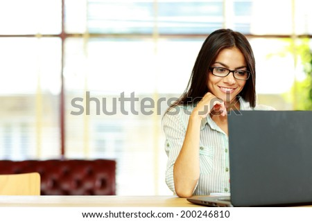 Smiling businesswoman working on the laptop at office - stock photo