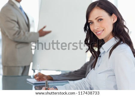 Smiling businesswoman writing in a notebook during a presentation